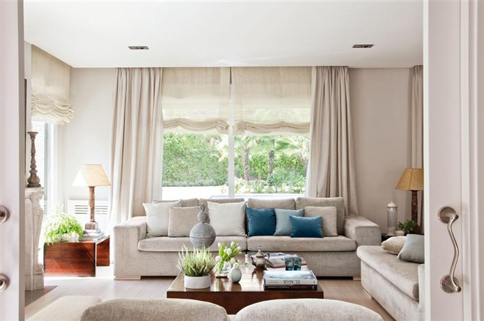 Una sala de estar luminosa en beiges y azules for Cortinas turquesas salon