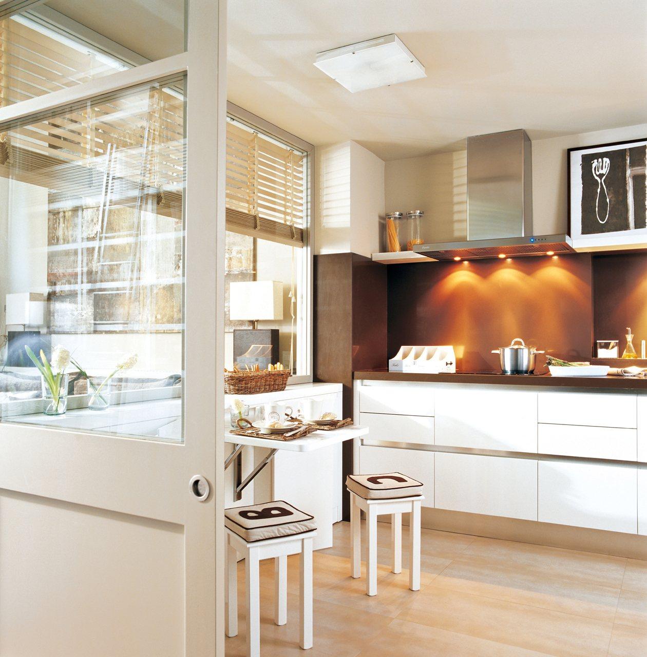 cocina blanca y marrn con una pequea mesa como office