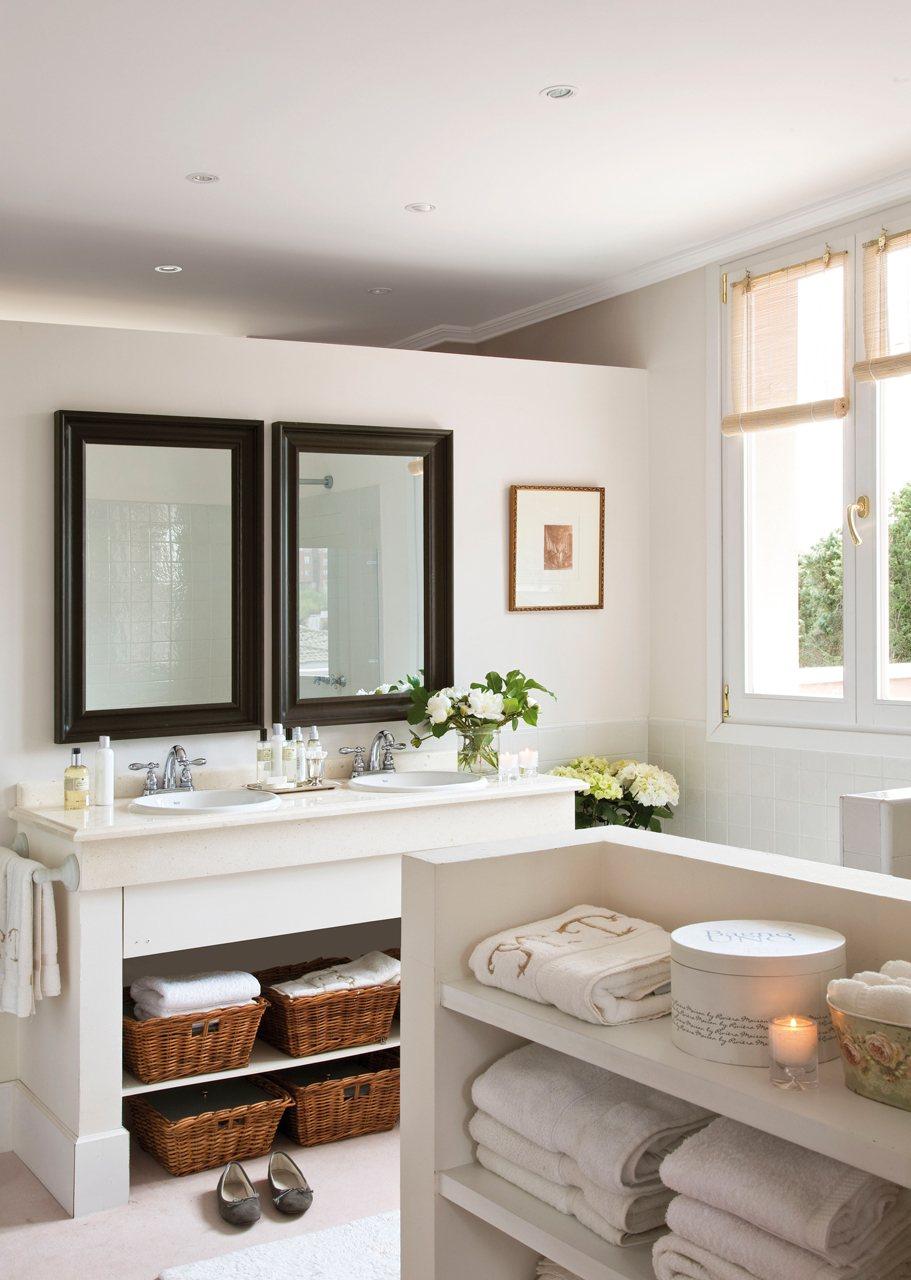 Gran espejo con tres focos de luz sobre un lavamanos blanco en una ...