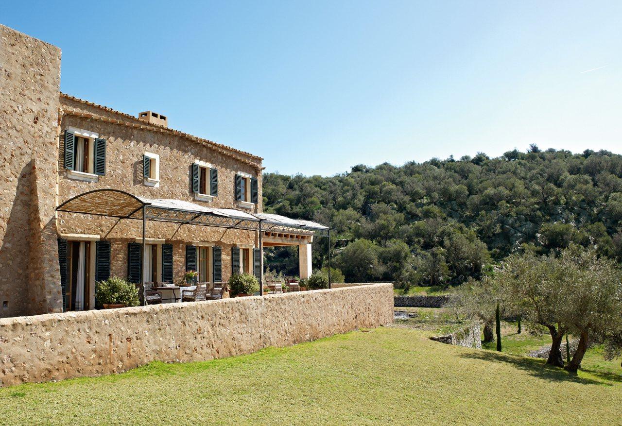 Casa r stica con paredes de piedra y porche con techo de for Cocinas rusticas mallorquinas