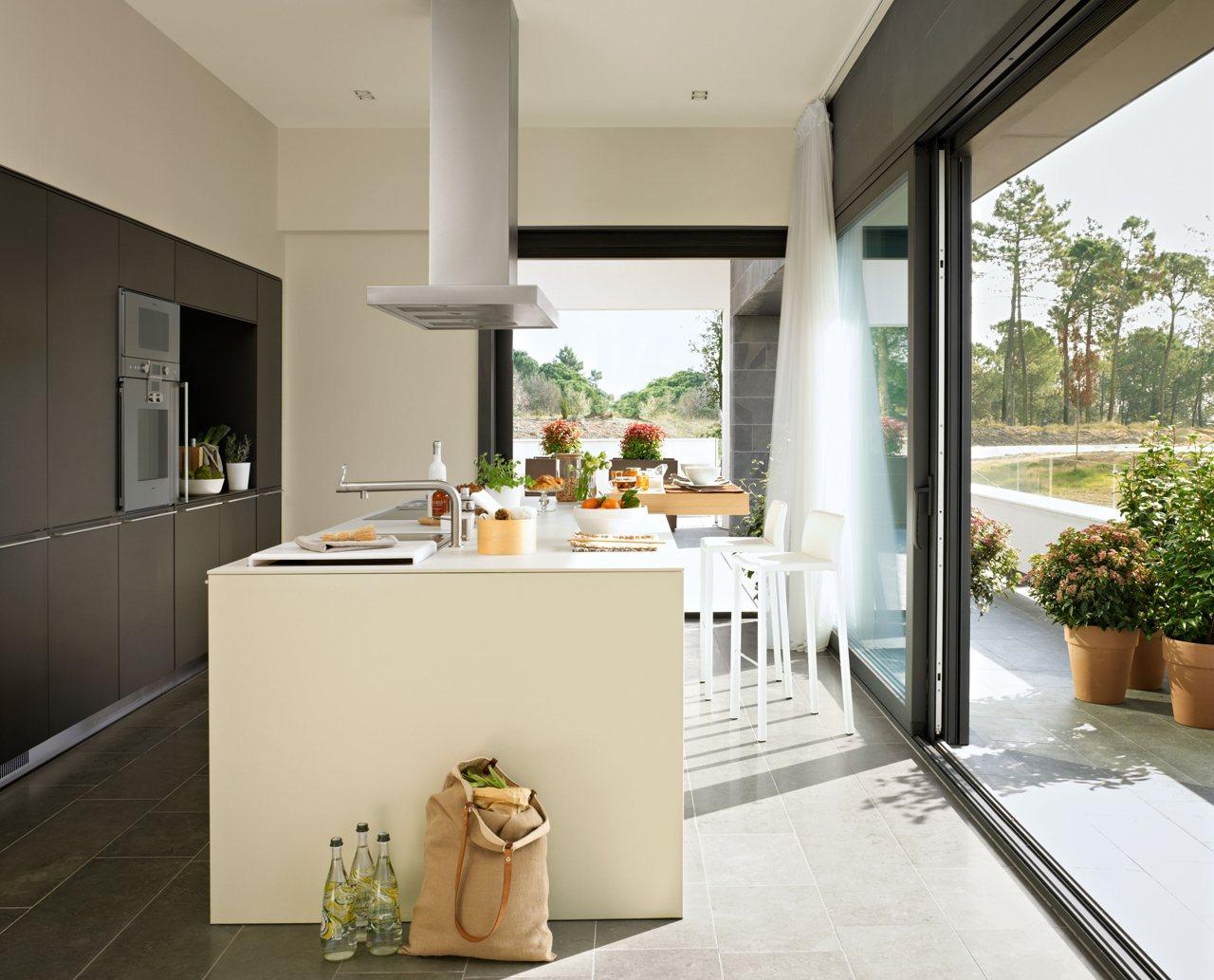 Una cocina con isla luminosa y familiar for Cocinas con salida al patio