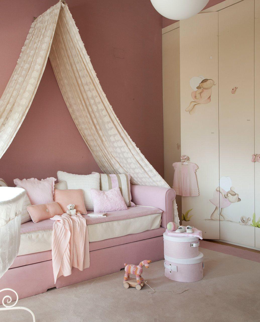 cama rosa y blanca con mosquitero junto a un gran armarios con dibujos de hadas