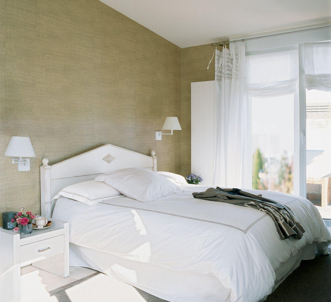 dormitorio con cabecero blanco zona de cama