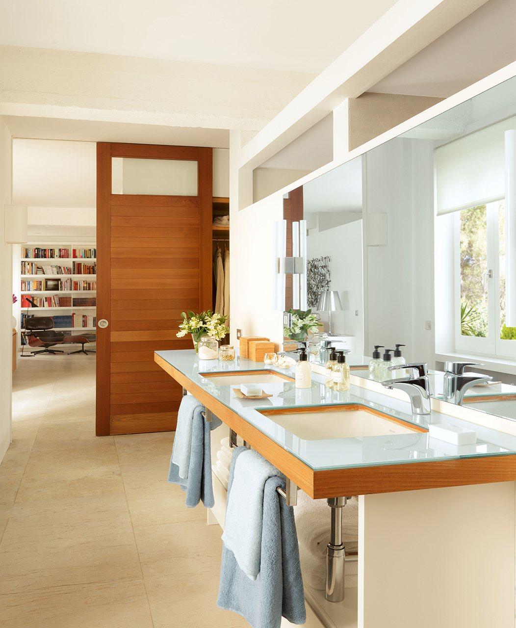bao con dos lavabos sobre una encimera de madera y cristal y una puerta corredera de madera hacia una sala de estar
