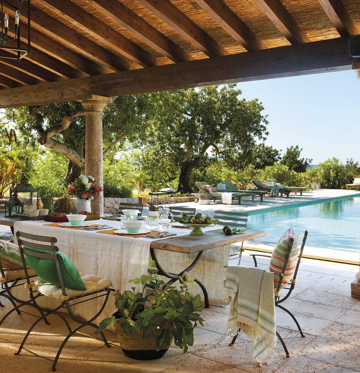 Comedor de verano exterior al lado de la piscina. Porche con vigas de madera, columnas y comedor junto a la piscina