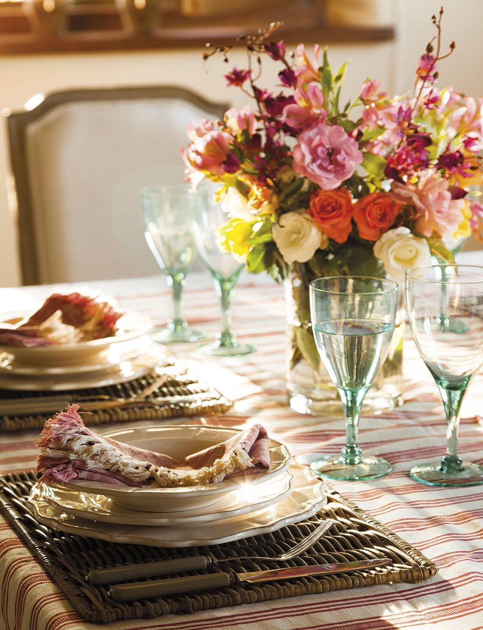 Detalle servicio mesa con copas de cristal verdosas. Sobre la mesa