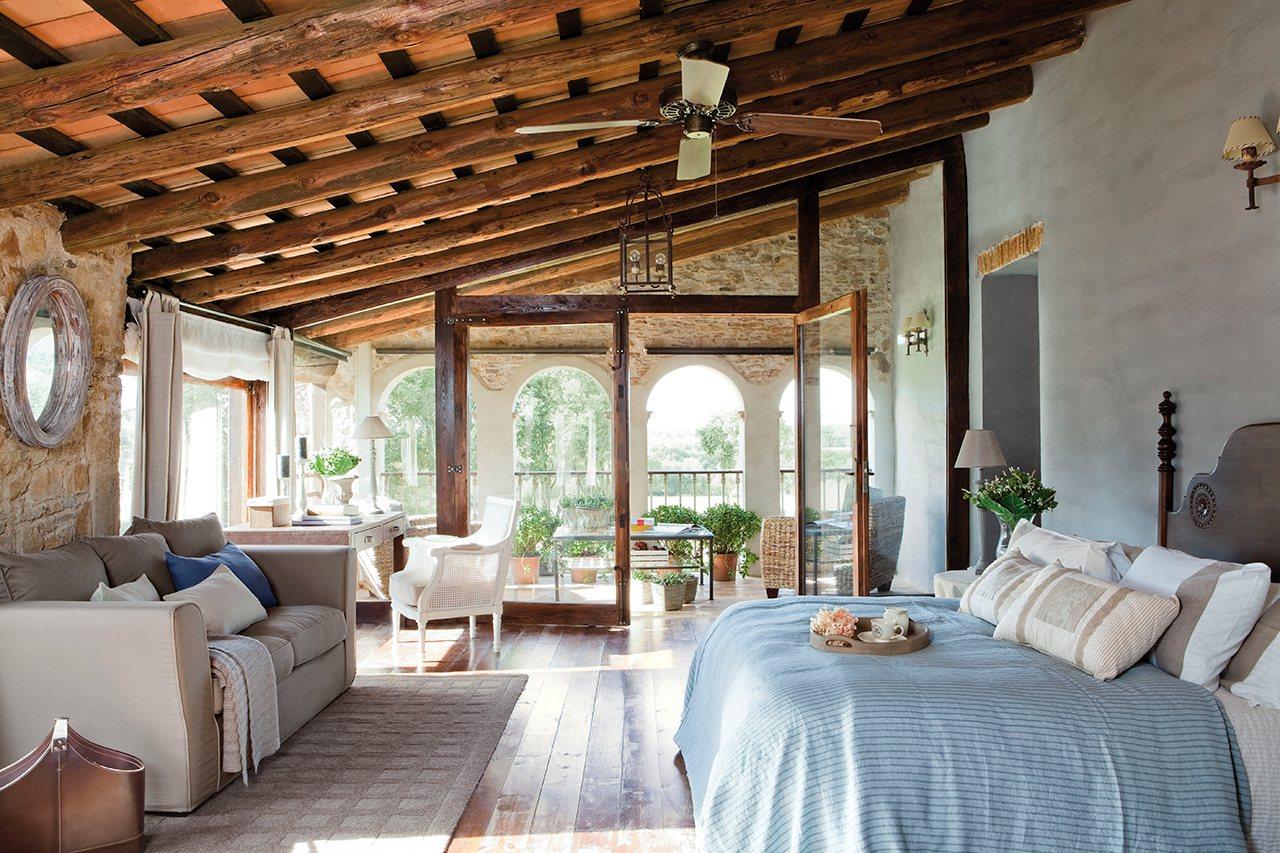 dormitorio con paredes de piedra vista techos de madera y arcos dormitorio con vigas
