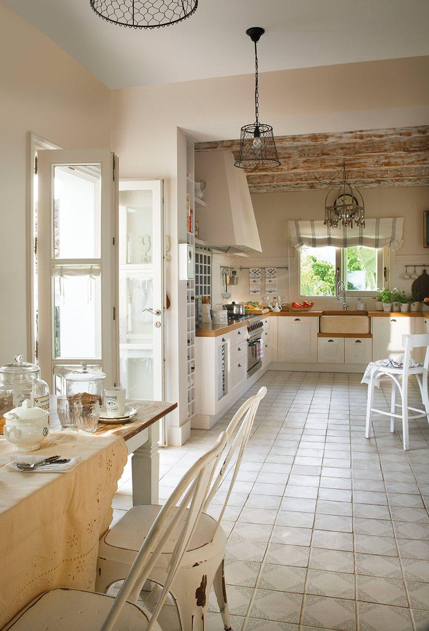 Cocina en tonos blancos con encimera de madera, suelo hidráulico y vigas en el techo. La cocina