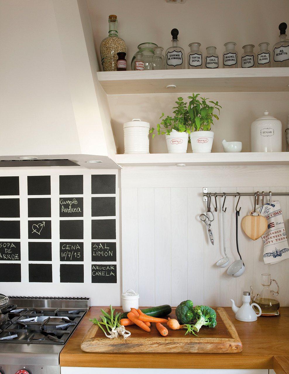 Detalle de cocina con pizarra bajo la campana. Blanco y madera