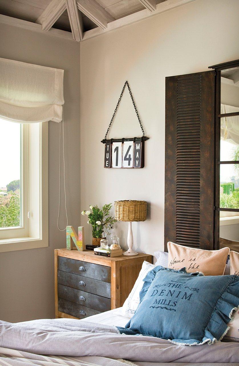 Detalle de rincón de dormitorio con cojines, lámpara con pantalla de mimbre y calendario. Dormitorio juvenil