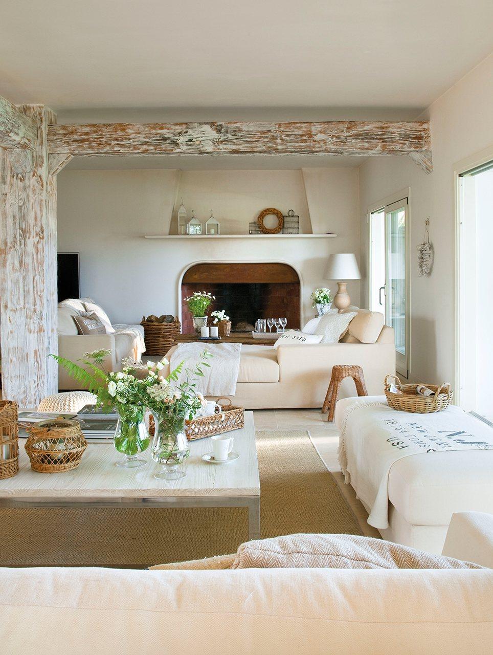 Salón con viga pintada en blanco, chimenea y grandes ventanales que comunican al jardín. En el salón