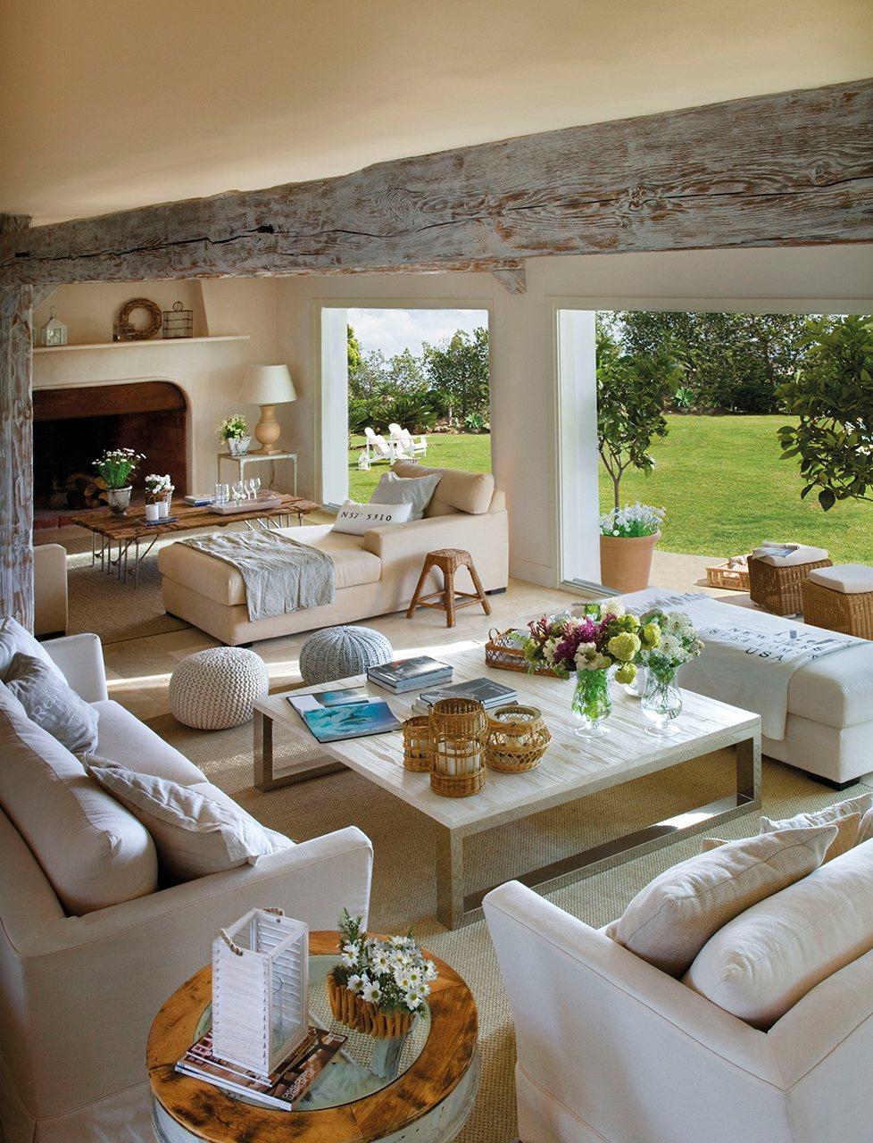 Salón con viga pintada en blanco, chimenea y grandes ventanales que comunican al jardín. Muy luminoso