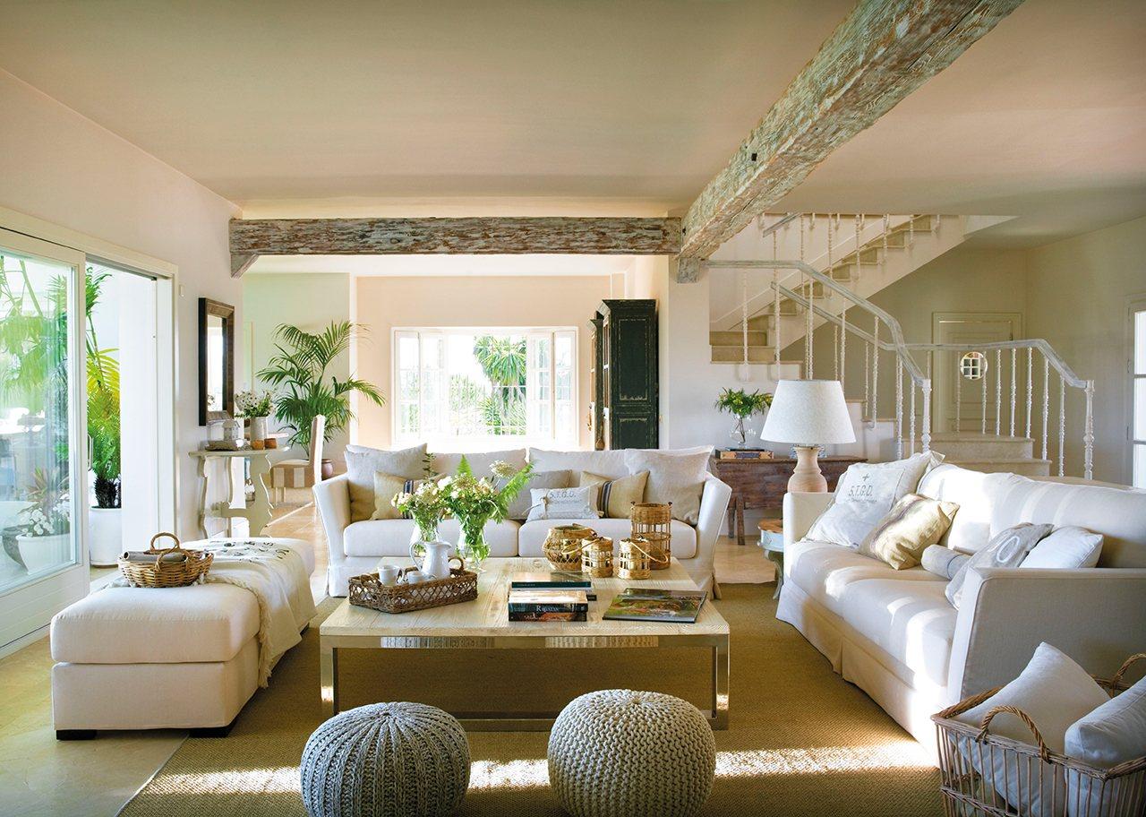 Salón con viga pintada en blanco, sofás blancos y grandes ventanales que comunican al jardín. Para conversar