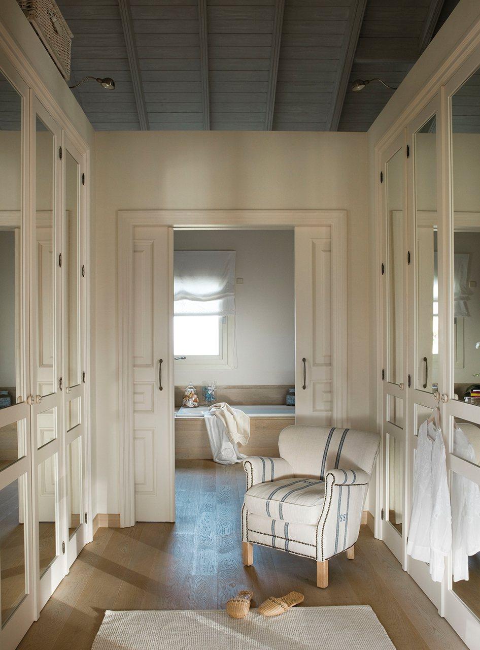 Vestidor con armarios empotrados a ambos lados y puertas correderas al fondo que dan al baño. En el vestidor