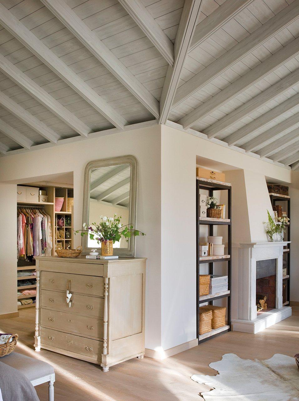 Zona de vestidor y chimenea en dormitorio con techo abuhardillado. Mucho almacenaje