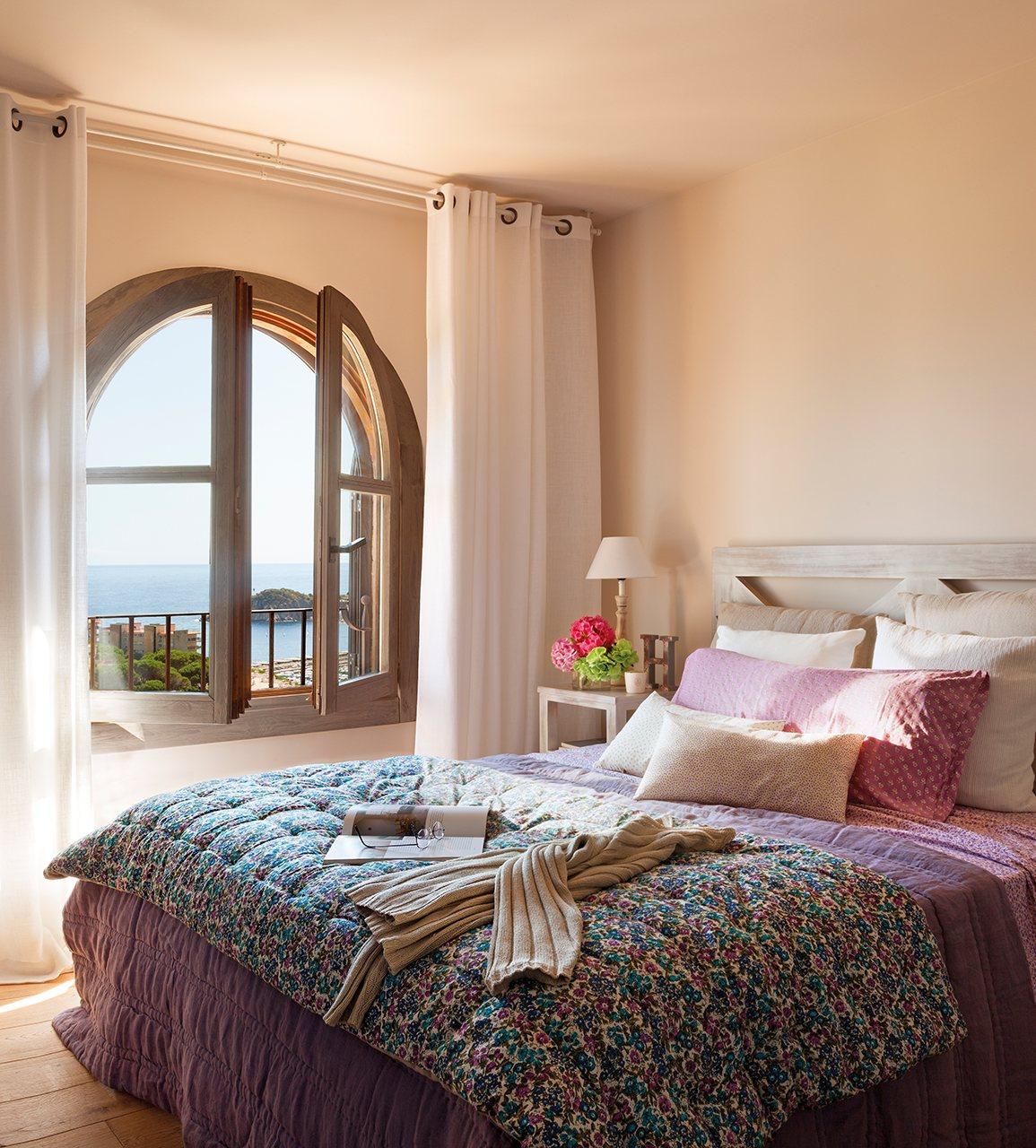 dormitorio con ventana en arco y vistas al mar dormitorio principal con ropa de cama