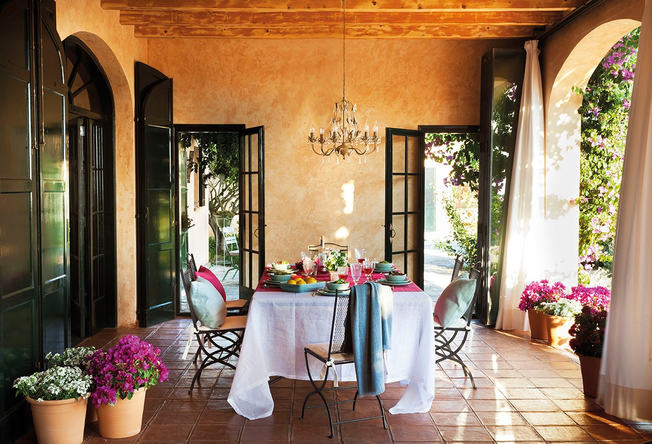 Comedor de verano en el porche. Comedor en el porche con detalles en fucsia y con una lámpara de araña en el techo