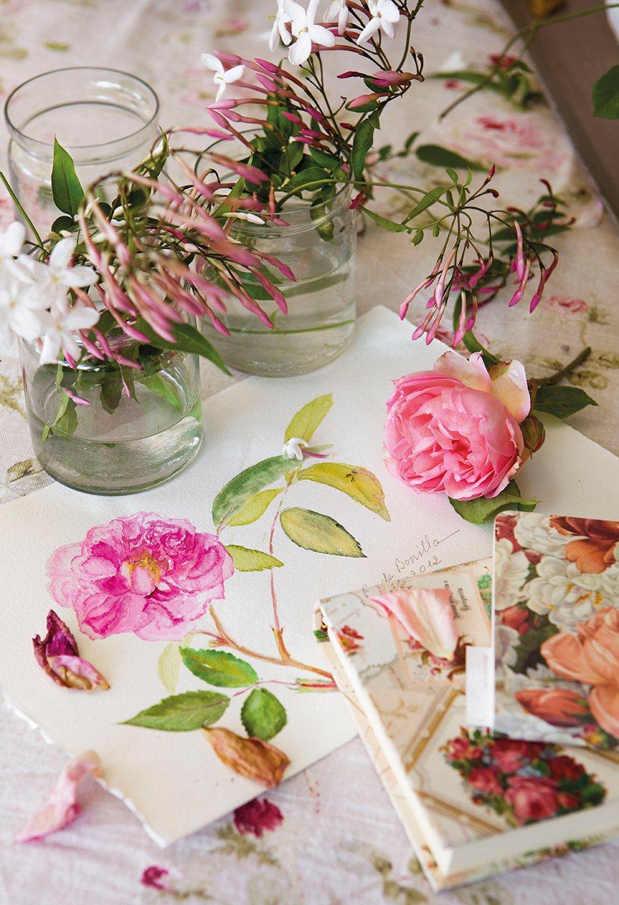 Flores en jarrones de cristal junto a un dibujo en acuarela de una flor