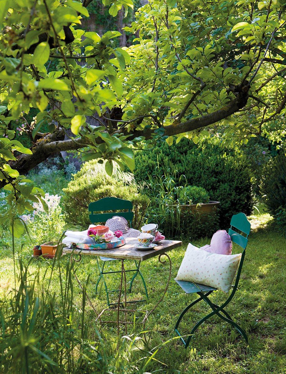Zona de estar con una mesa y sillas junto a un manzano