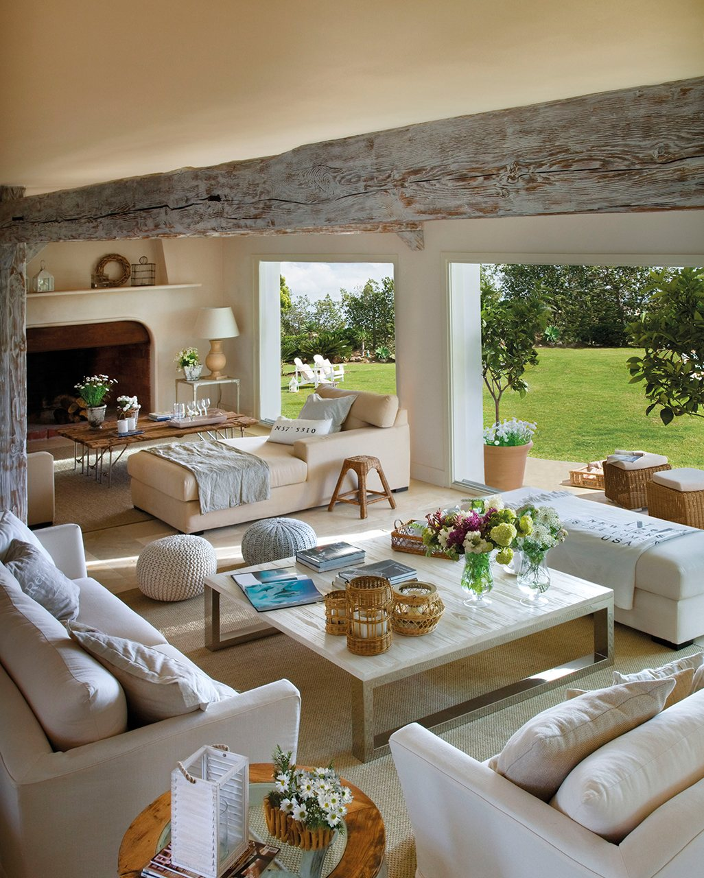 Salón con completa zona de tertulia, chimenea y grandes ventanas al jardín