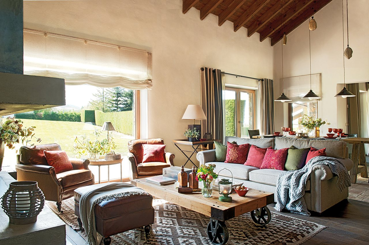 Salón con un gran ventanal con sofá gris, mesa de centro industrial y cojines en rojo
