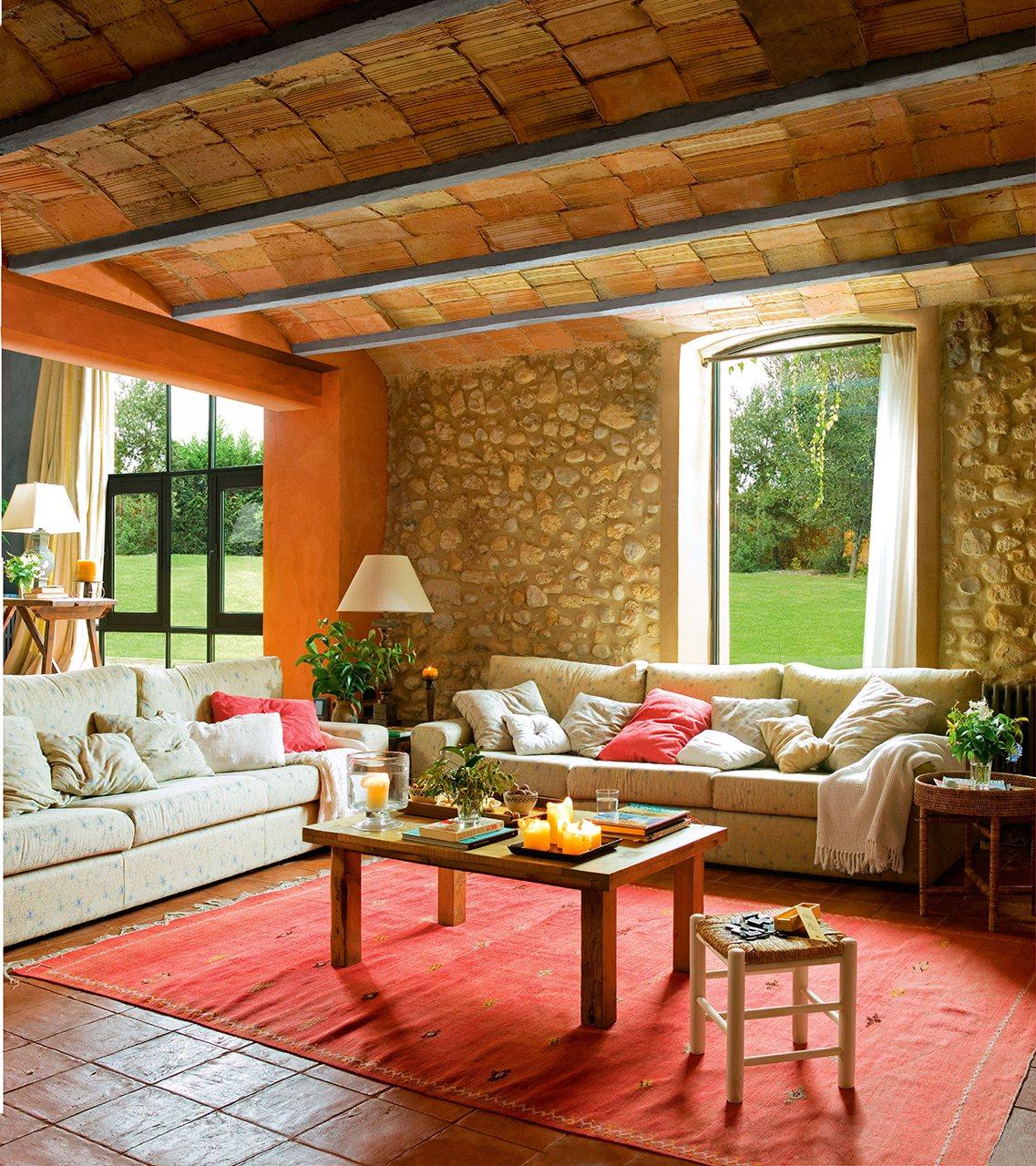 Salón rústico con paredes de piedra, vuelta catalana y sofás en beige