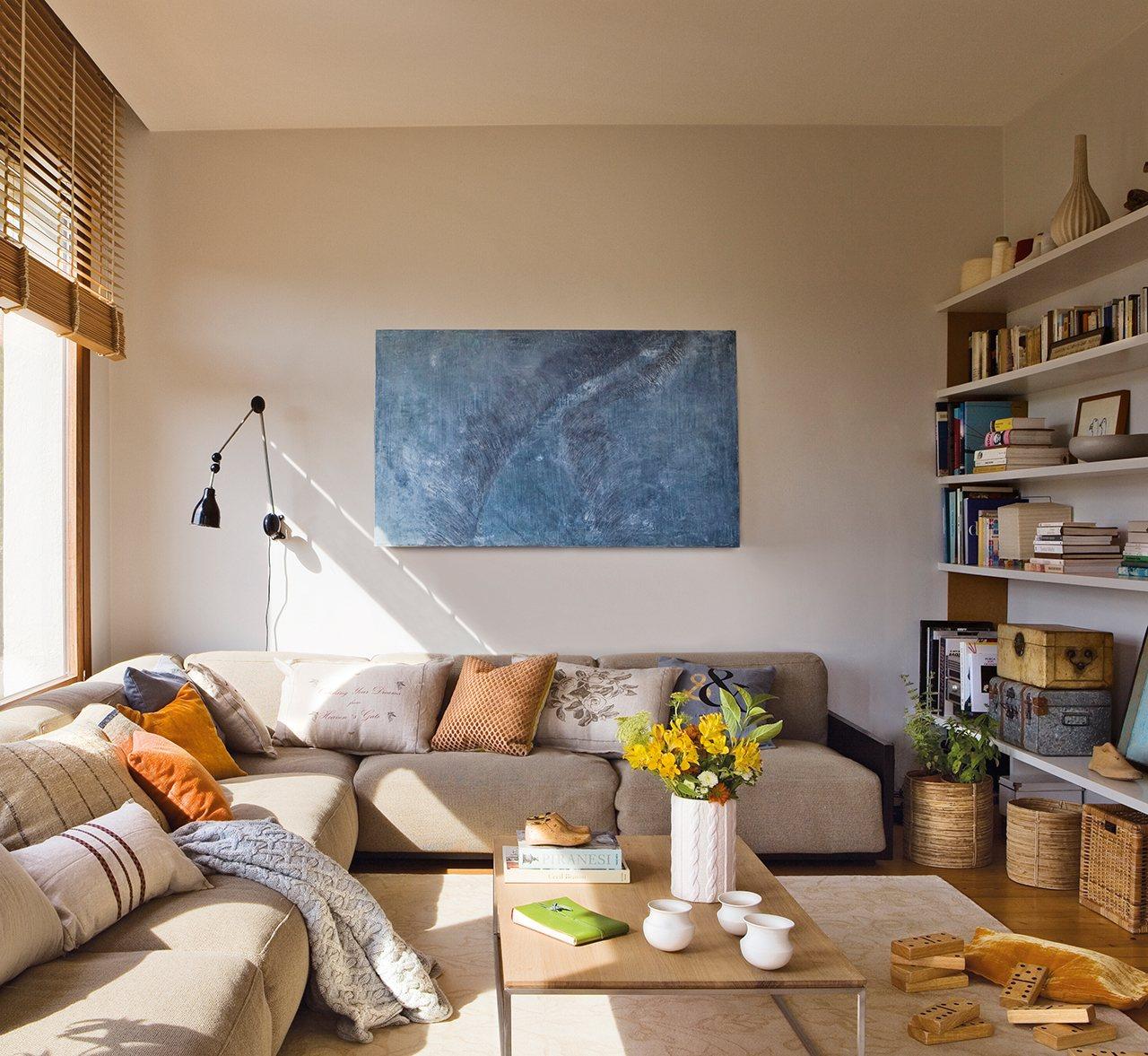 Salón con sofá rinconero y librería. Un cuadro con truco