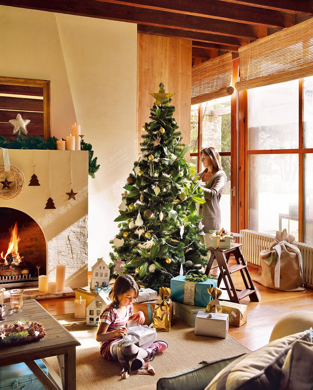 mujer decorando el abeto y nia envolviendo regalos saln rstico con rbol de navidad y
