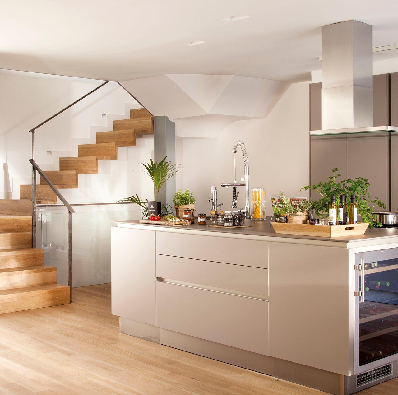 cocina con mobiliario en gris y escaleras de madera al fondo en la isla