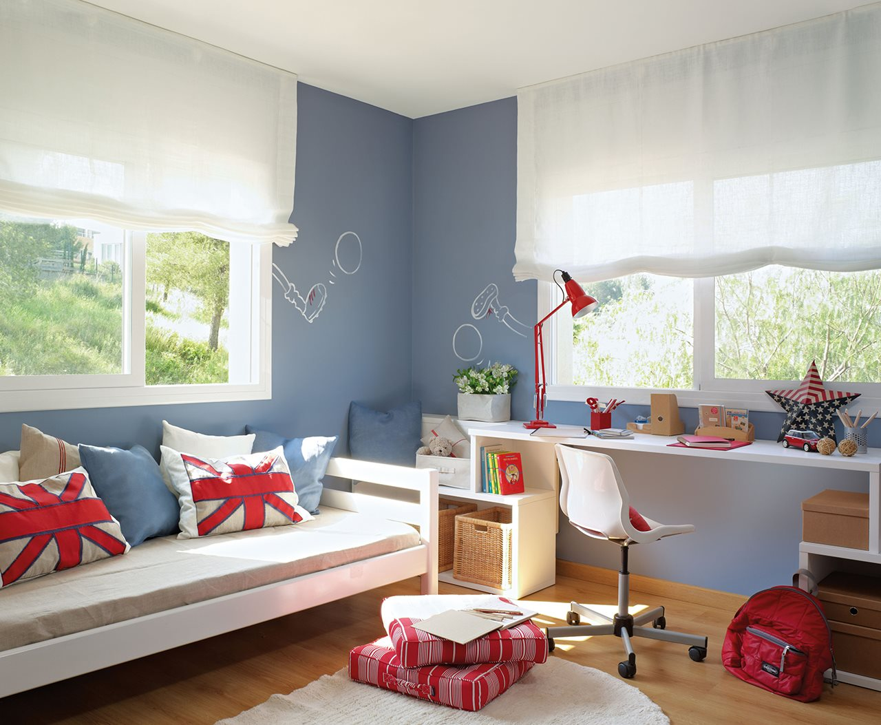 dormitorio infantil con escritorio y cama bajo las ventanas