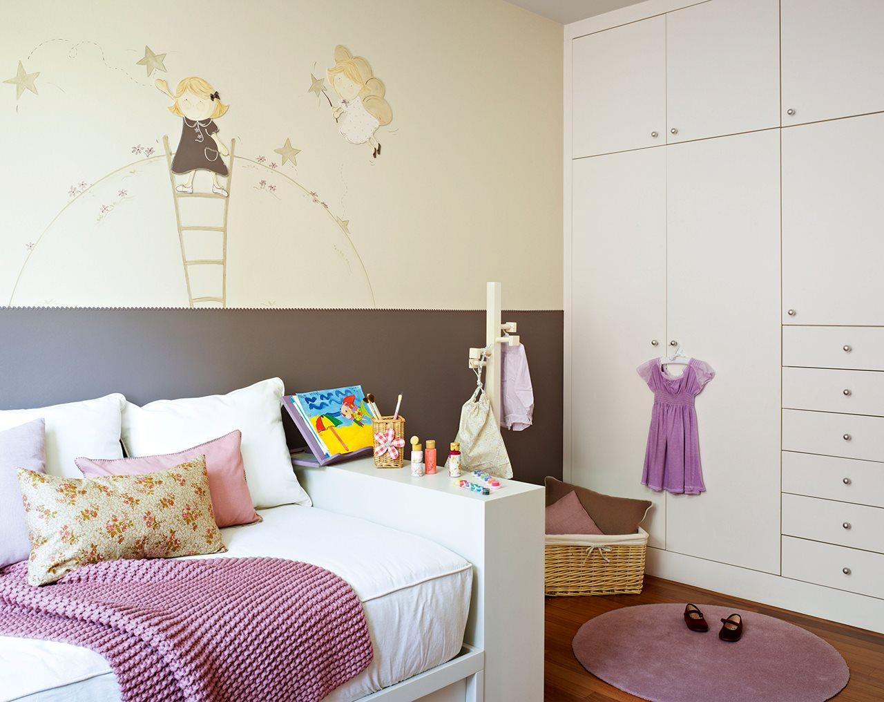 dormitorio infantil con dibujos en las paredes y un gran armario blanco