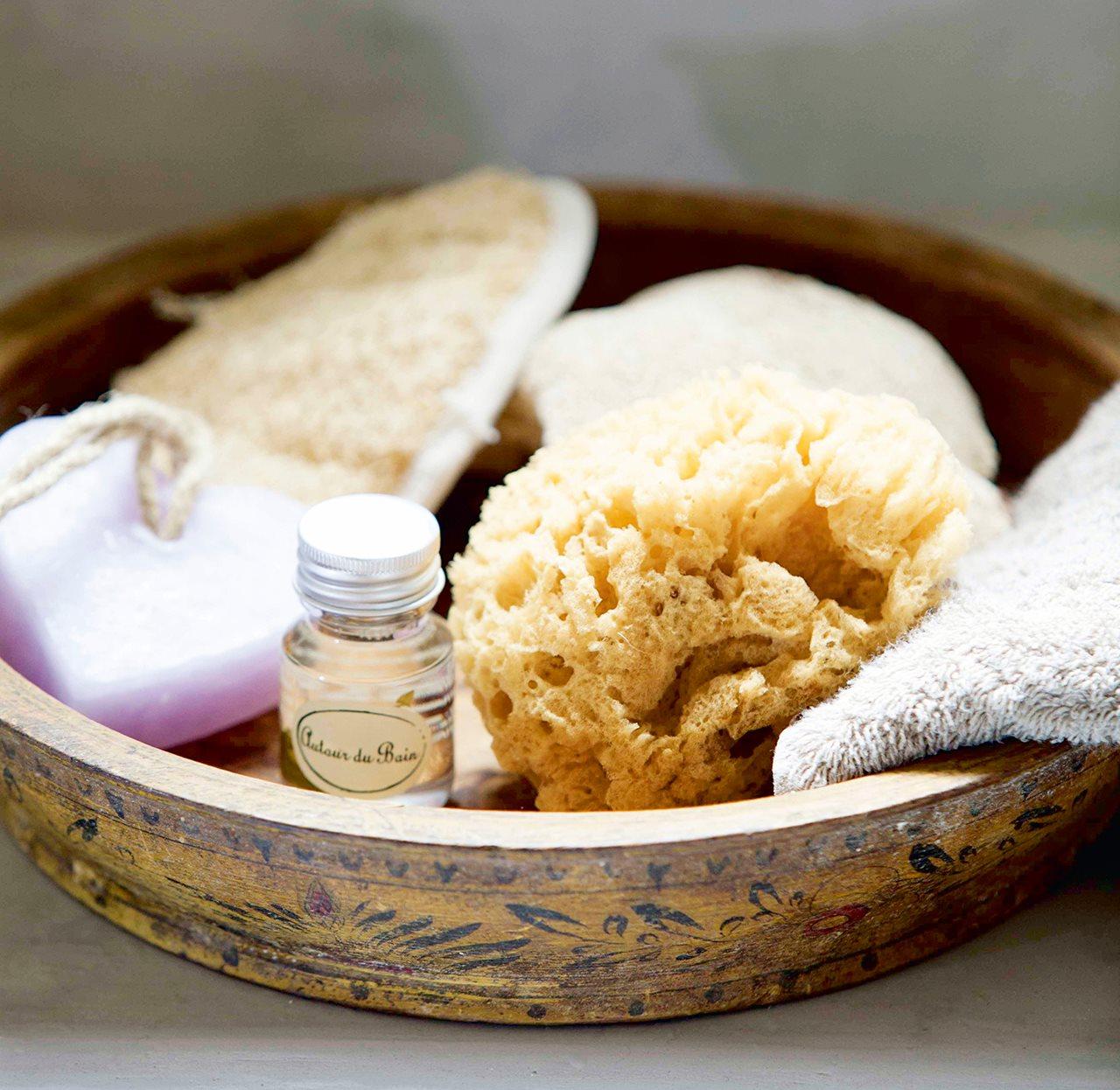 Detalle de cesto con esponjas y jabones. Desinfecta las esponjas.