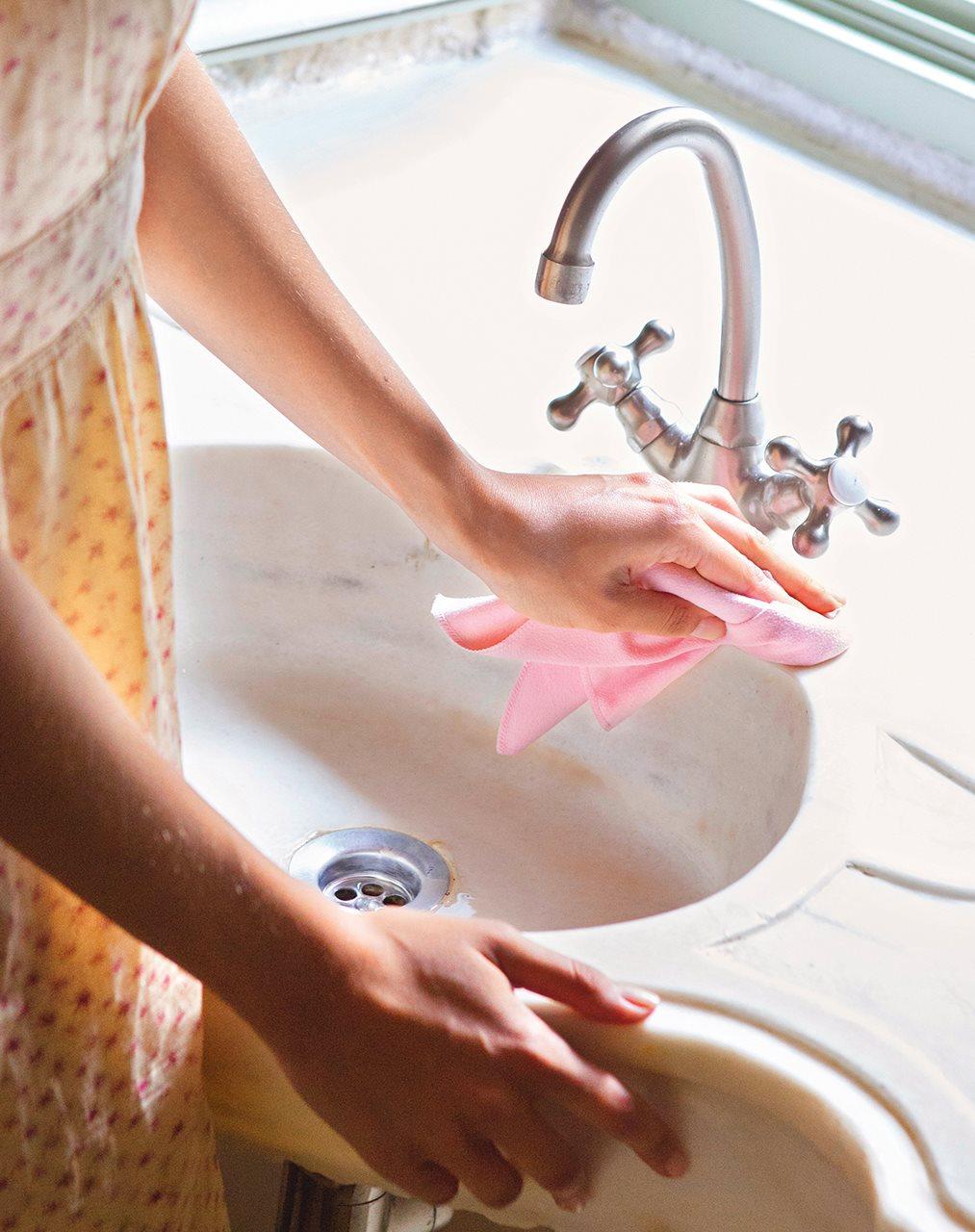 Detalle de mujer fregando lavamanos. Vinagre por las tuberías.