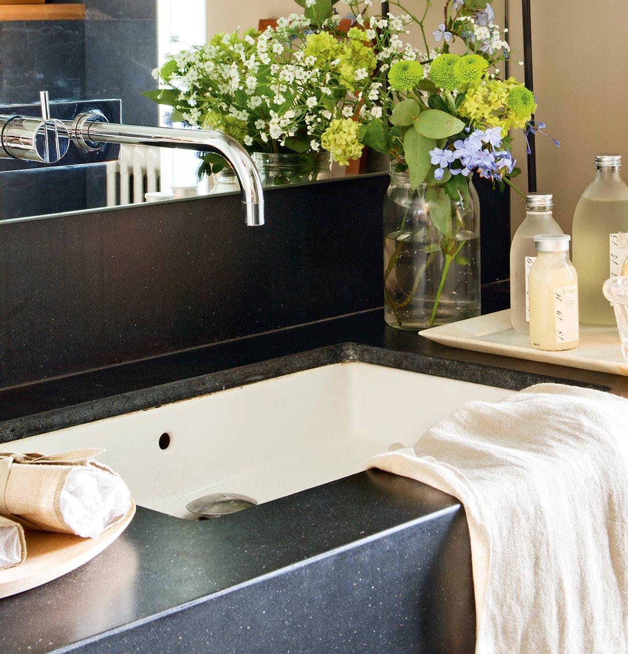 detalle de lavamanos con encimera de mrmol negro lavamanos