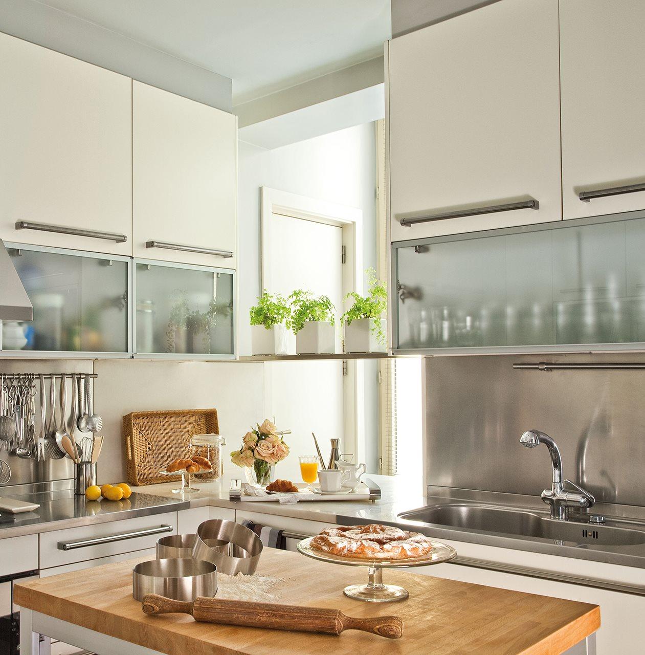 detalle de cocina en blanco con armarios hasta el techo y vitrinas