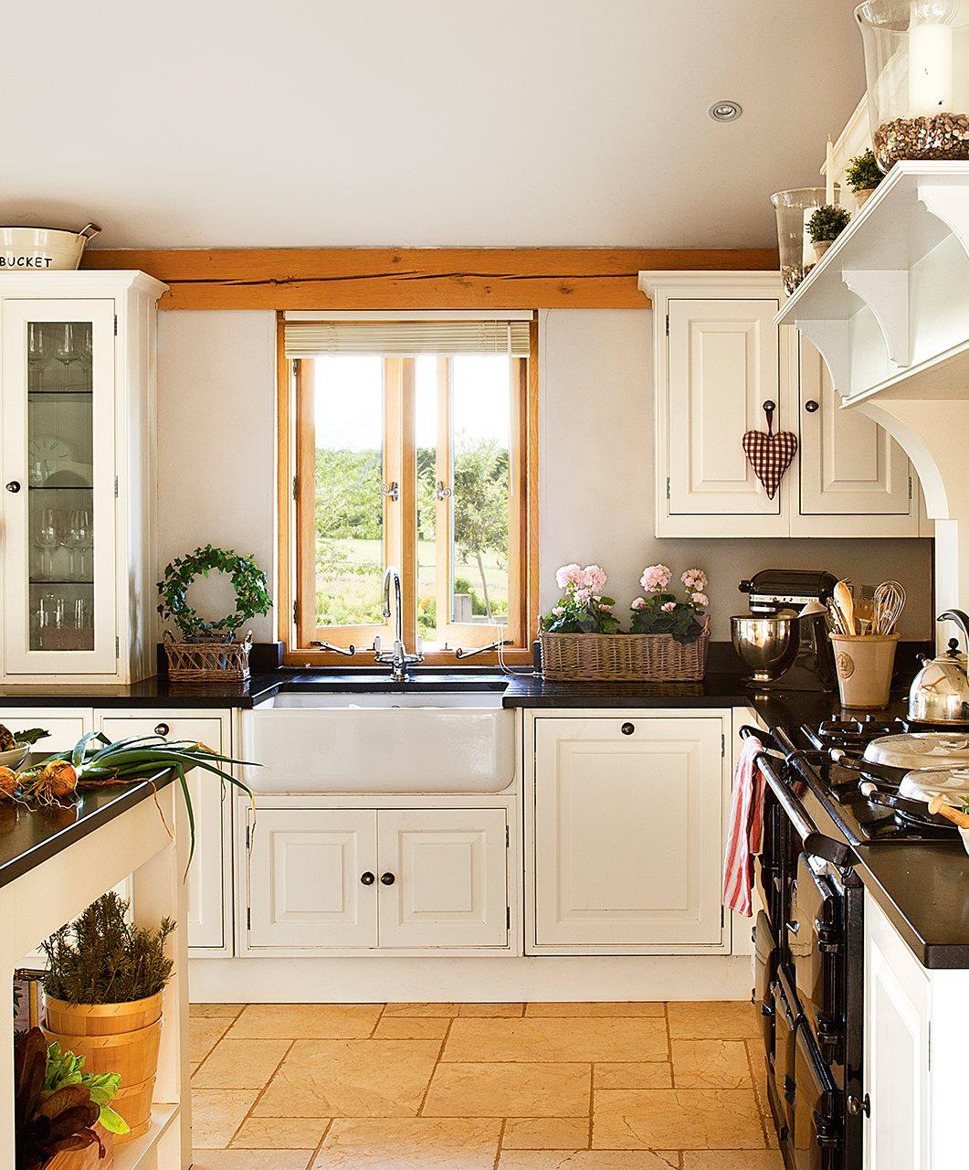 cocina con armarios blancos y encimera de granito negra