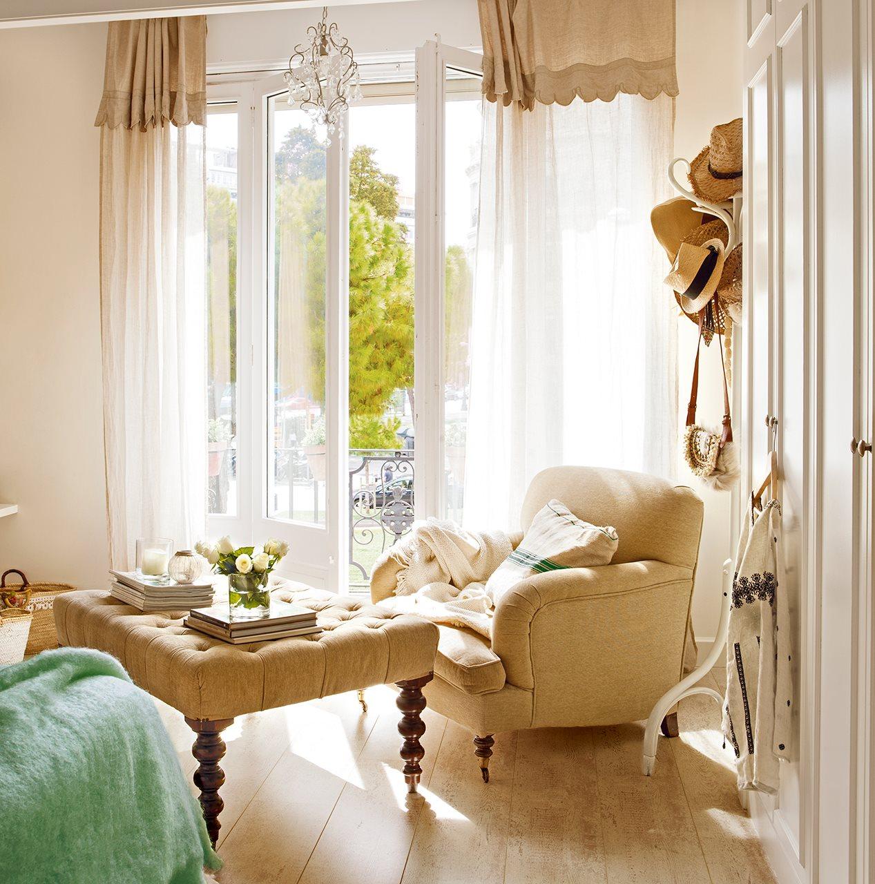 Salón con butaca y puf tapizado estilo chester a modo mesilla auxiliar. salon tonos tostados y butaca con gran ventanal