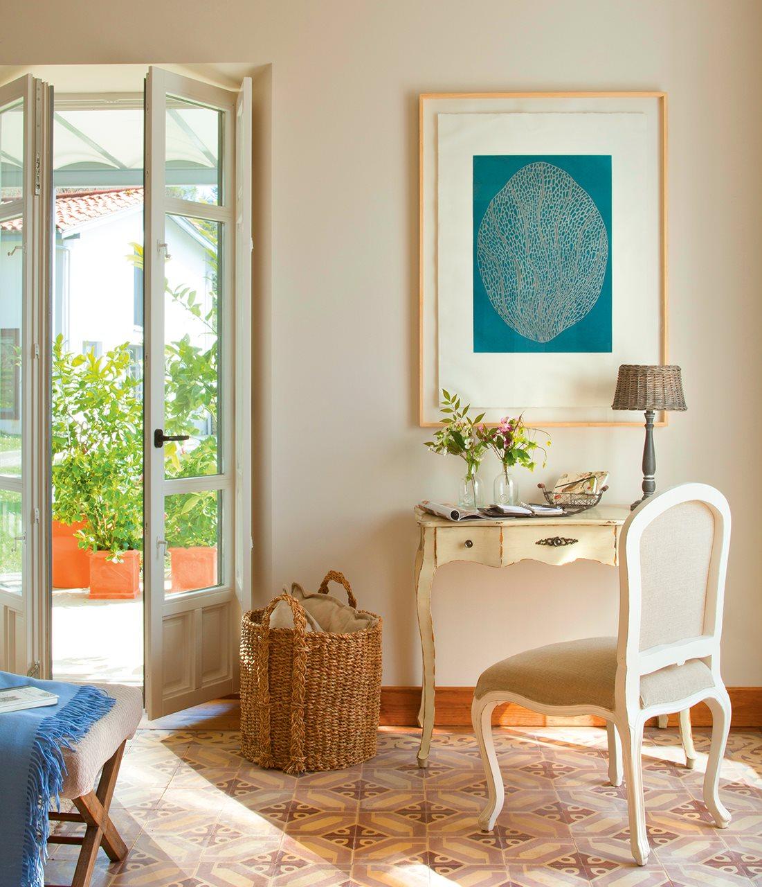 Escritorio con cuadros y flores encima. Colgado sobre un mueble.