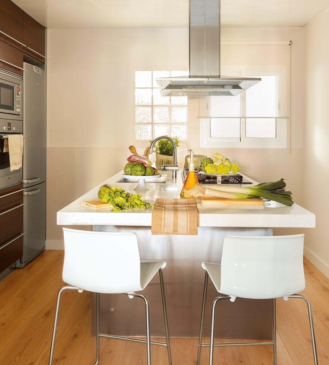 Cocina con zona de desayuno en la isla. Cocina blanca con una isla con dos taburetes