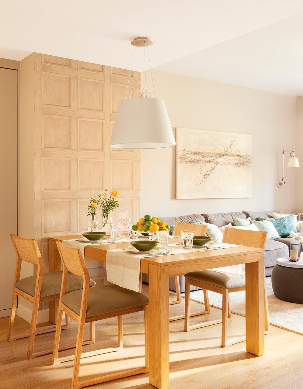 Comedor con papel pintado que imita un panel de madera . Comedor junto al salón con mobiliario de madera y vajilla en verde