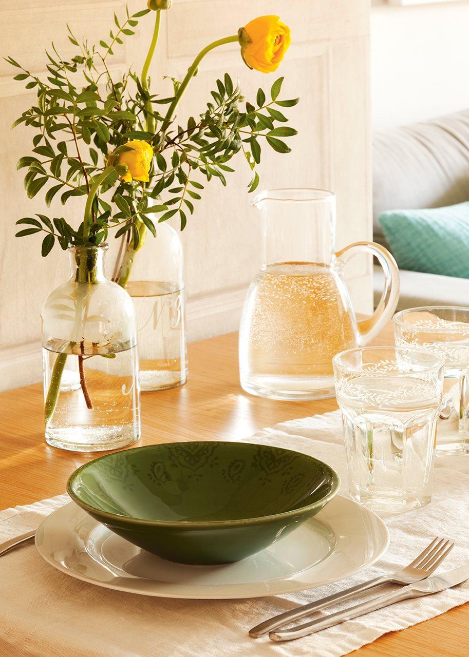 Detalle de vajilla y jarrón con flores. Detalle de la vajilla verde y flores sobre la mesa del comedor