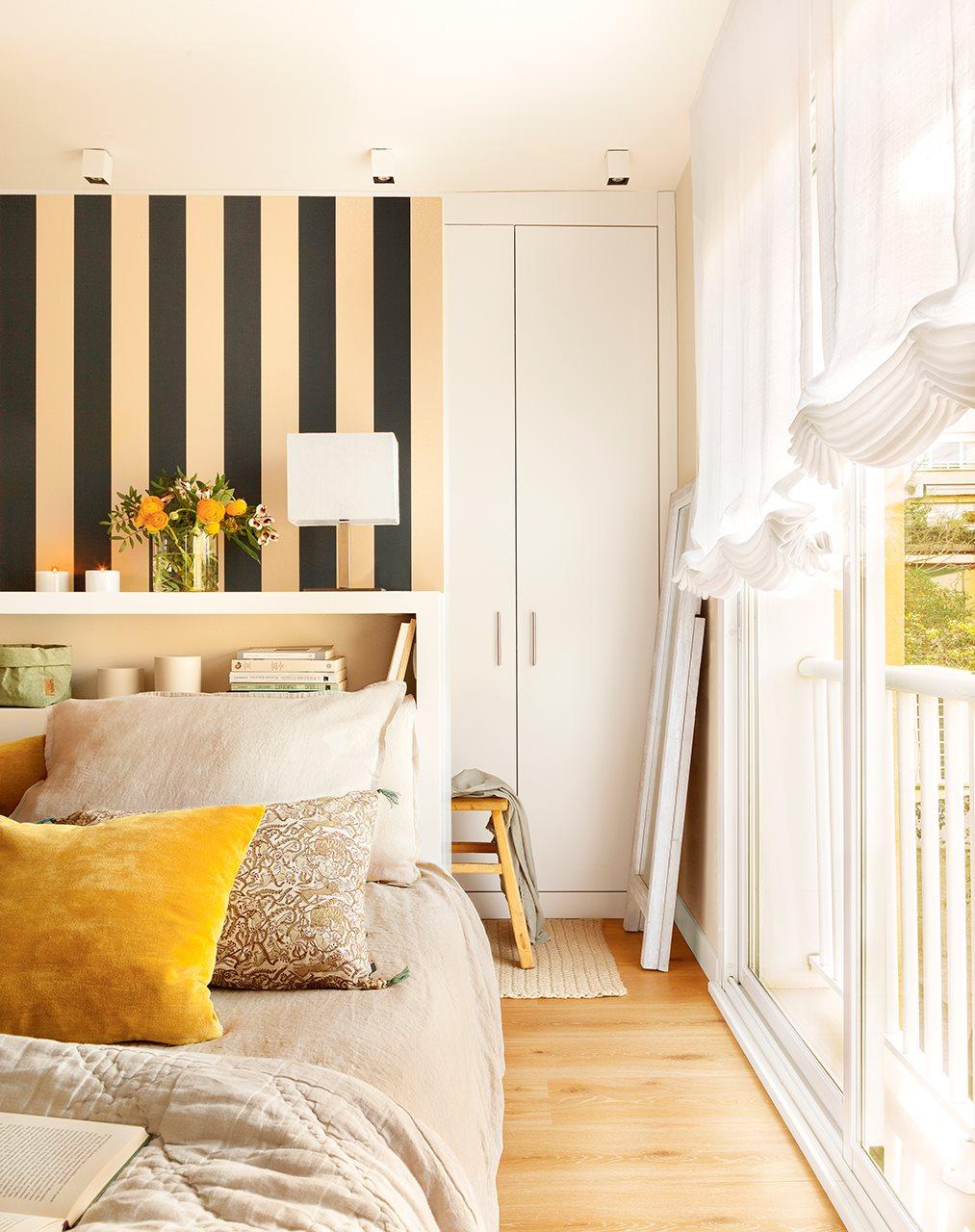 Dormitorio con papel de rayas en el cabecero. Dormitorio con cama con cabecero blanco y papel pintado a rayas en la pared