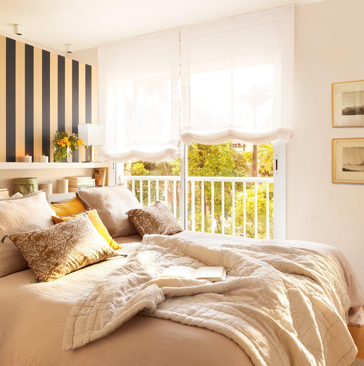 Dormitorio con papel de rayas en el cabecero. Dormitorio con ropa de cama en beige y dorado y estores blancos a las ventanas