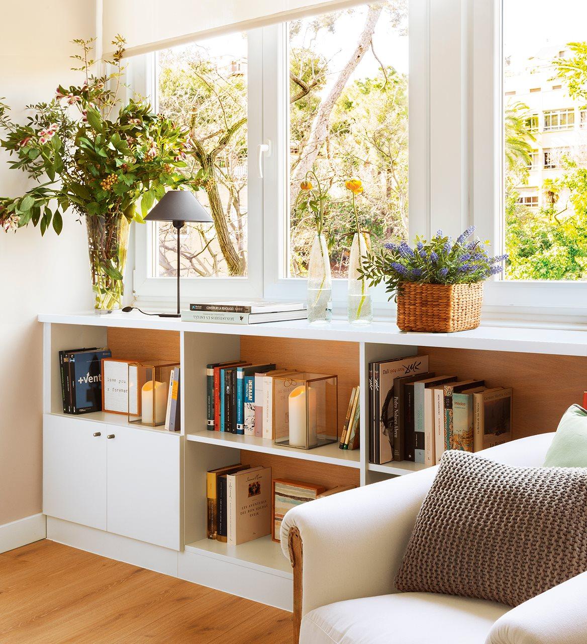 Librería bajo la ventana. Librería blanca bajo la ventana con flores y plantas encima