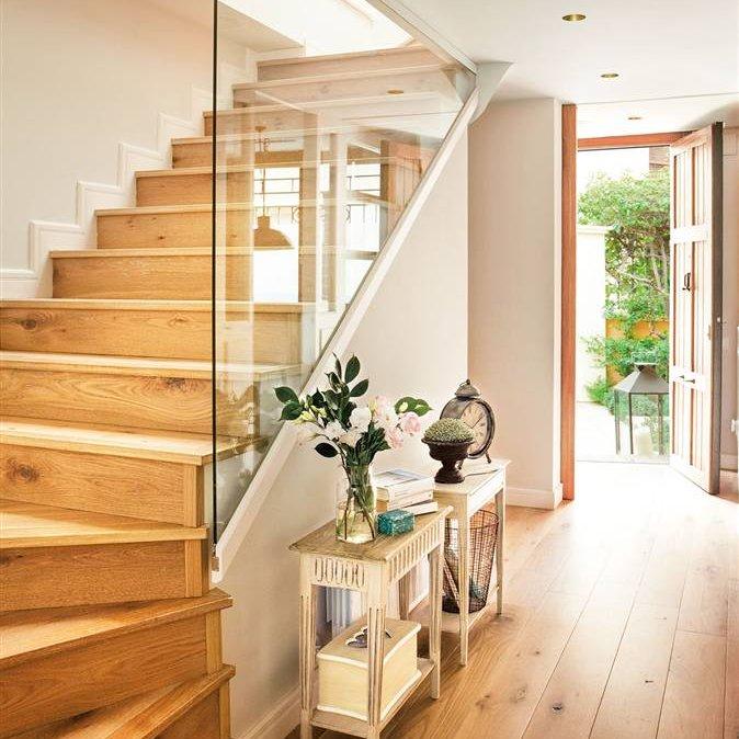 3f30ef7ae Recibidor con suelo de parquet y escaleras en madera con separación de  cristal y exentas de