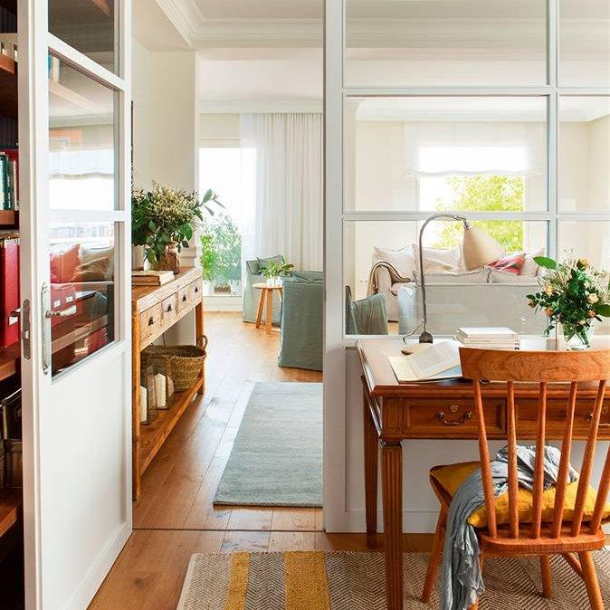 vista del estudio con la mesa y la silla hacia el estar separado por cerramiento