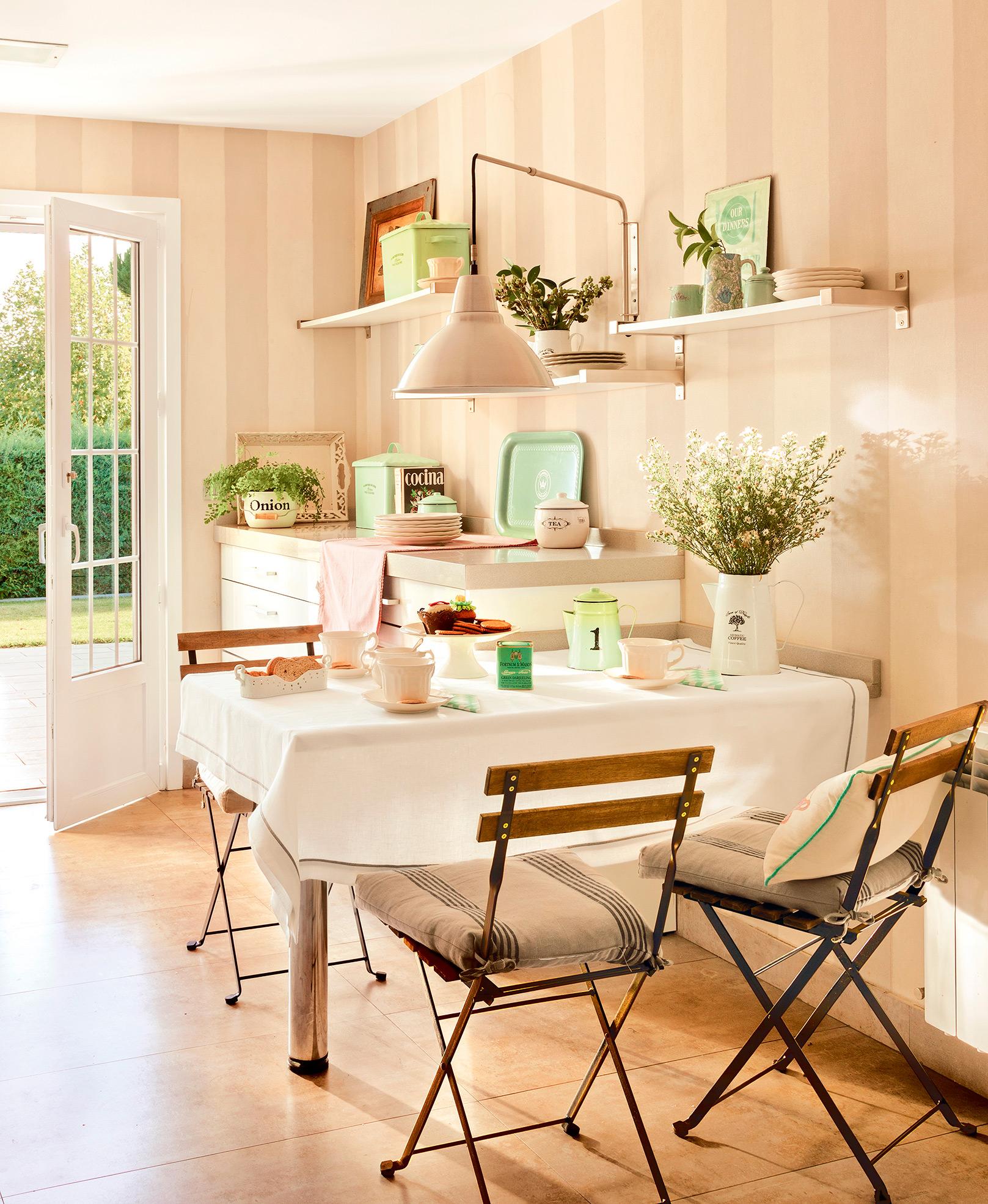 Comedor con mesa fijada a la pared, sillas plegables, accesorios vintage y estanterías