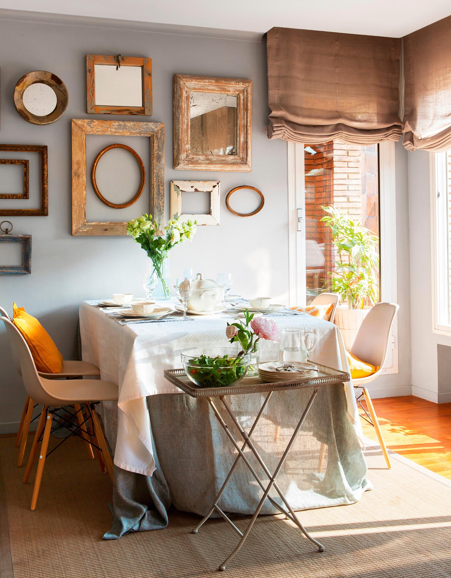 Comedor con sillas Eames, bandeja de metal con pie de tijera plegable, cuadros madera decapada y doble mantel
