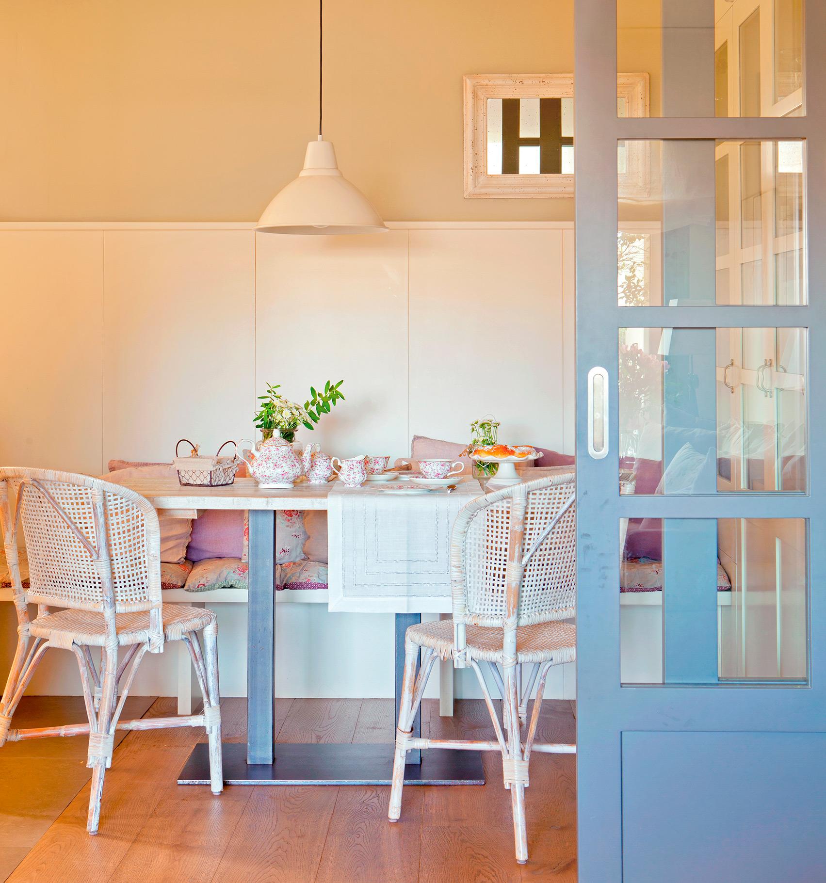 Comedor country con banco, sillas de mimbre, mantelería vintage, cojines cottage y puerta corredera