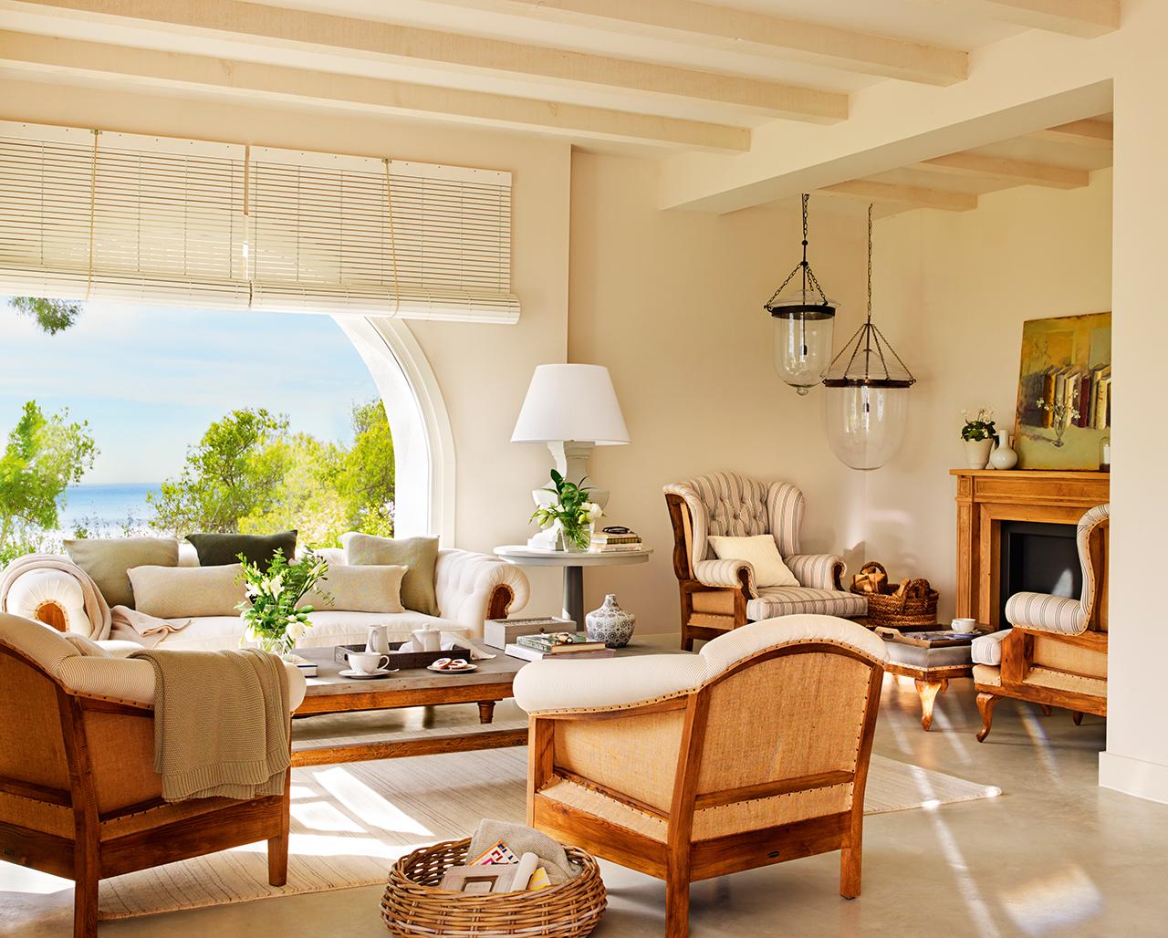 Salón en tonos beige con amplias butacas y chimenea